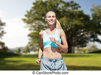 smiling young woman running or jogging over park - fitness,...