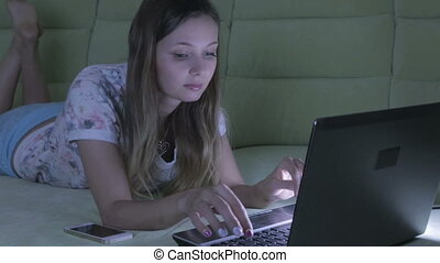 Beautiful girl lying on couch working at her laptop. She answers the call on a smartphone.