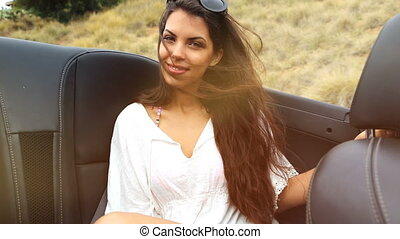 young woman at the backseat of a convertible. summer feeling