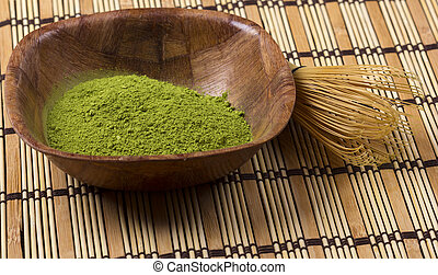 Green matcha in a bowl with wisk