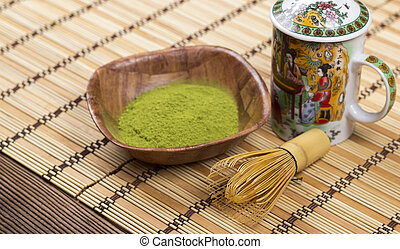 Green matcha in a bowl with wisk and ornamented teapot