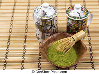 Green matcha in a bowl with wisk and ornamented teapots