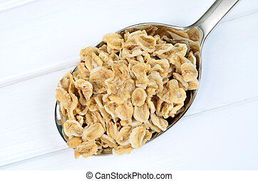 Organic oatmeal in silver spoon on white wooden table