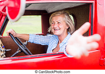 Close up of senior woman inside vintage pickup truck - Close...