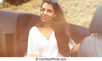 young woman at the backseat of a convertible. summer feeling...