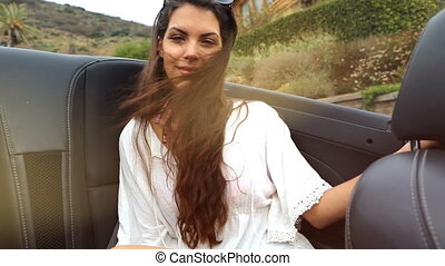 young woman at the backseat of a convertible summer feeling...