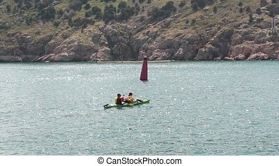 Two people kayaking - two person kayak floating on the sea...