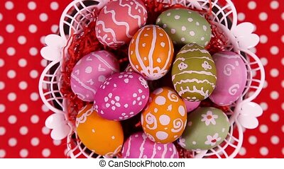 Easter eggs in basket rotating on the red tablecloth