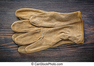 Pair of working gloves on vintage wooden board directly...