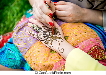Picture of human hand being decorated with henna tattoo,...