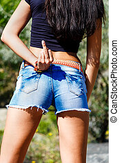 Sexy girl in jeans shorts show middle finger up. - Sexy girl...