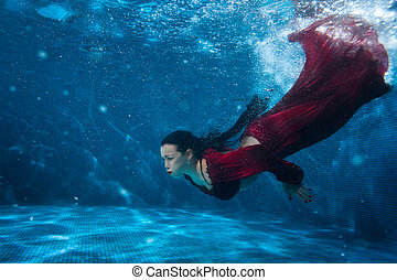 Woman in the pool underwater. - Woman in red dress dives...