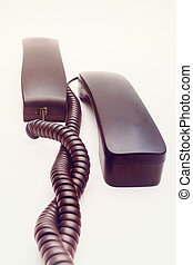Telephone receiver with cable on white background