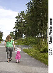 Obese mother and child walking on a forest path on a...