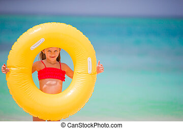 Adorable girl with inflatable rubber circle on white beach -...