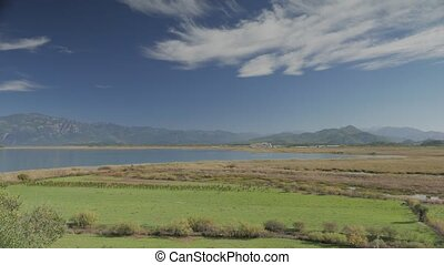 Summer landscape of green valley near lake with blue sky...