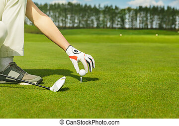 hand placing golf ball on tee - male hand in glove placing...