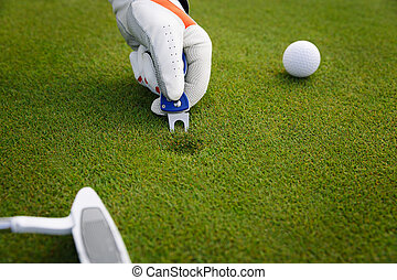 Marking golf ball position at the green. Focus on marker. -...