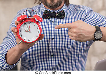 Businessman holding alarmclock - Close-up picture of...