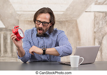 Businessman holding alarmclock and checking time with his...
