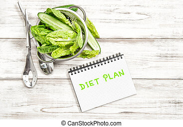 Green salad leaves and vegetables with diet plan journal