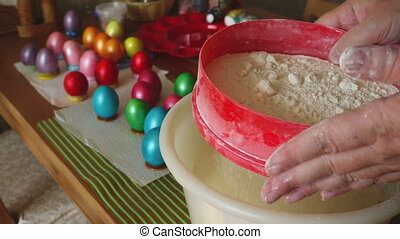 A woman sifts flour for the preparation of Easter cakes