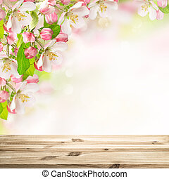 Wooden table top on blossoming apple tree blurred background...