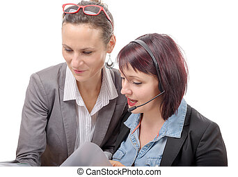Two young smiling women working together with notebook