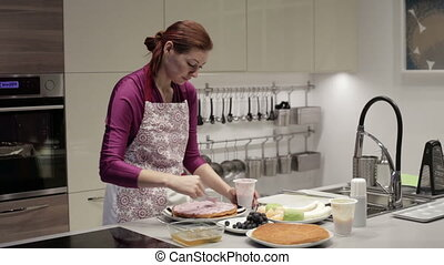The woman preparing sponge cake - The woman in an apron in...