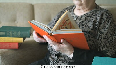 Old woman sitting on a chair reading a thick book