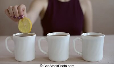 Putting lemon into three tea cups