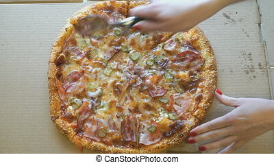 Hand slicing a meat pizza into slices using knife - Female...