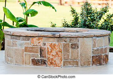 Outdoor flagstone firepit with landscape in background. -...