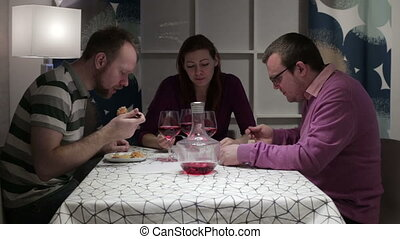 Three person having dinner at the table - Friends sit at the...