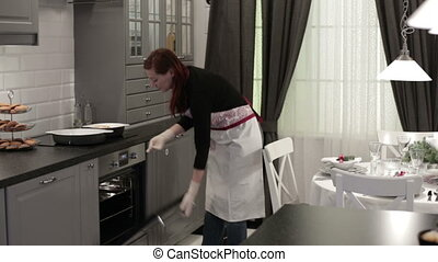 Woman puts plates of food in the oven - The woman in an...