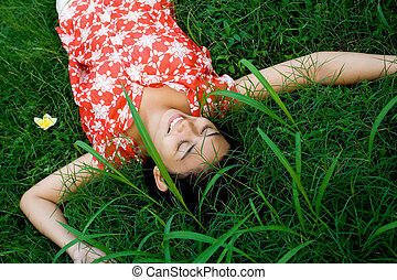 asian woman lying on green grass