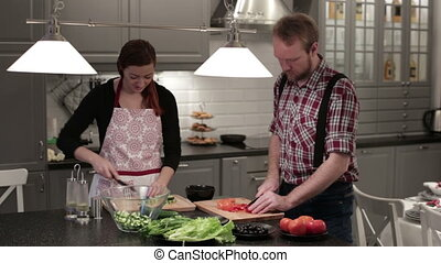 Couple preparing a salad - The woman in an apron in the...
