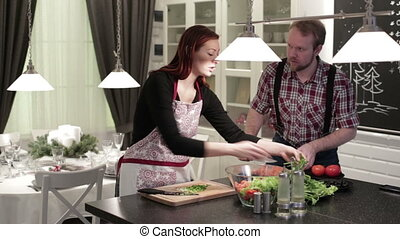 Happy couple preparing salad