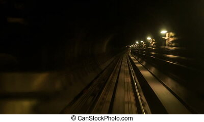 Camera Moves Forward along Metro Rails in Dark Tunnel