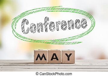 May conference sign on a wooden table with text