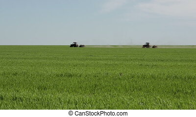 Two tractors on green farm field - Green agricultural field...
