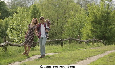 Summer Family Stroll - Photo of a young family enjoying a...