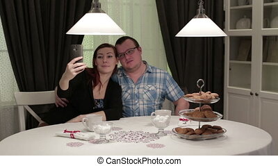Friends in cafe sitting at the table doing selfie