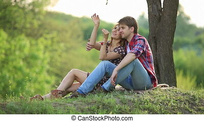 Loving couple on a meadow - Happy couple sitting on a green...