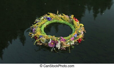 A grass and flower wreath floating on the water. Ethnic...