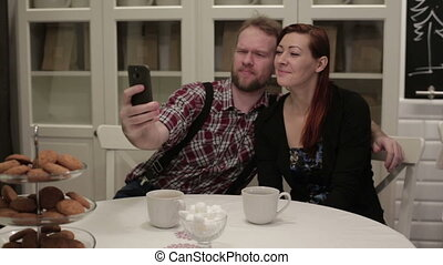 Happy couple sitting at the table doing selfie