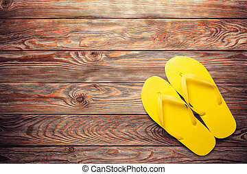 Yellow flip flops on a wooden background