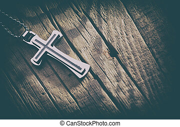 Silver cross on a wood background close up image