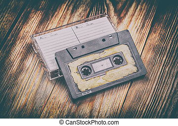 Old audio cassette on a brown wooden background