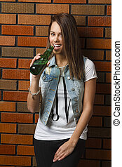 Taking a sip - underage girl, against a brick wall, taking a...